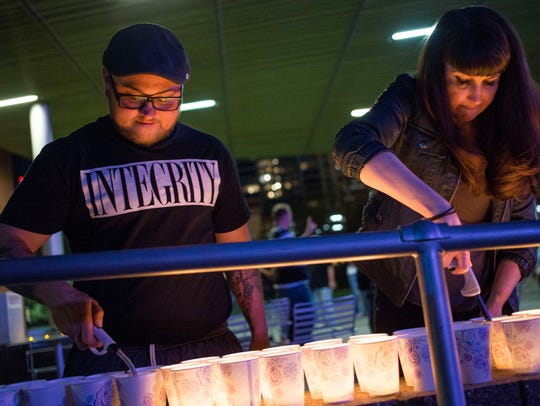 Beth Payne, right, and Mason Gallaway light candles