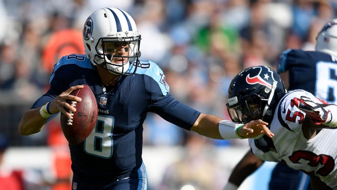 Titans quarterback Marcus Mariota (8) scrambles during the first half Sunday against the Texans.