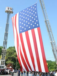 Crews prepare the 60- by 30-foot flag hung over Inkster