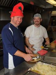 Matt Brewer and Joe Nixon prepare plates of food for