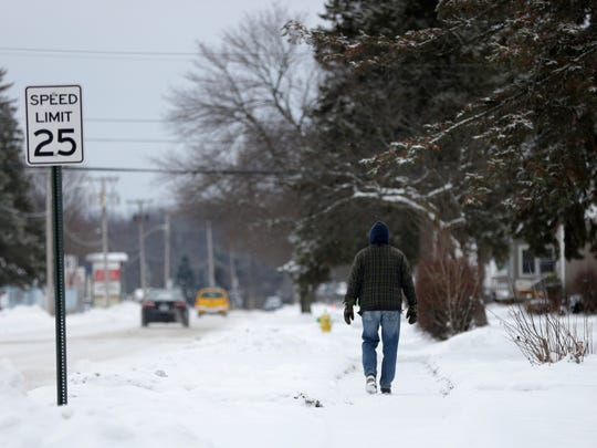 A man traverses a snowy sidewalk in-between flurries that combined will drop more than a foot of snow on the region Friday, December 16, 2016.