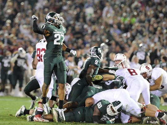 MSU defender Kurtis Drummond and the rest of the Spartan defense celebrate their key fourth down stop against Stanford in the fourth quarter at the Rose Bowl Jan. 1, 2014.