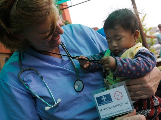 Nine-month-old Saina Suwal plays with the name tag of nurse practitioner Marilynn Bartley. Medical staff from the Delaware Medical Relief Team saw more than 300 patients during a clinic at Khwopa Higher Secondary School in Bhaktapur, Nepal, on Saturday.