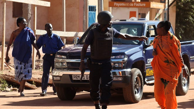 Malian security forces evacuate two women from an area Nov. 20, 2015, surrounding the Radisson Blu hotel in Bamako, Mali.