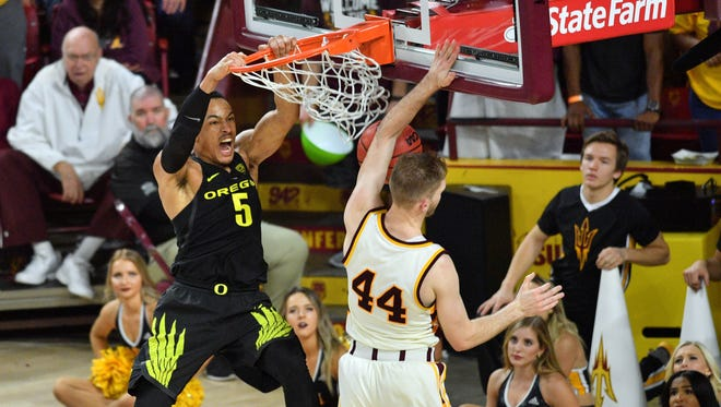 Oregon guard Elijah Brown dunks over Arizona State guard Kodi Justice during the second half at Wells-Fargo Arena in Tempe, Ariz.