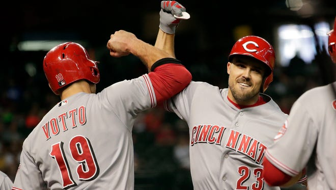 Cincinnati Reds' Adam Duvall (23) celebrates with Joey Votto (19) after hitting a grand slam against the Arizona Diamondbacks during the fourth inning of a baseball game Wednesday, May 30, 2018, in Phoenix.