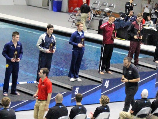 Ryan McClelland (second from left) takes his place on the stand after placing seventh off the 3-meter diving board in the D-III nationals held last month in Indianapolis.