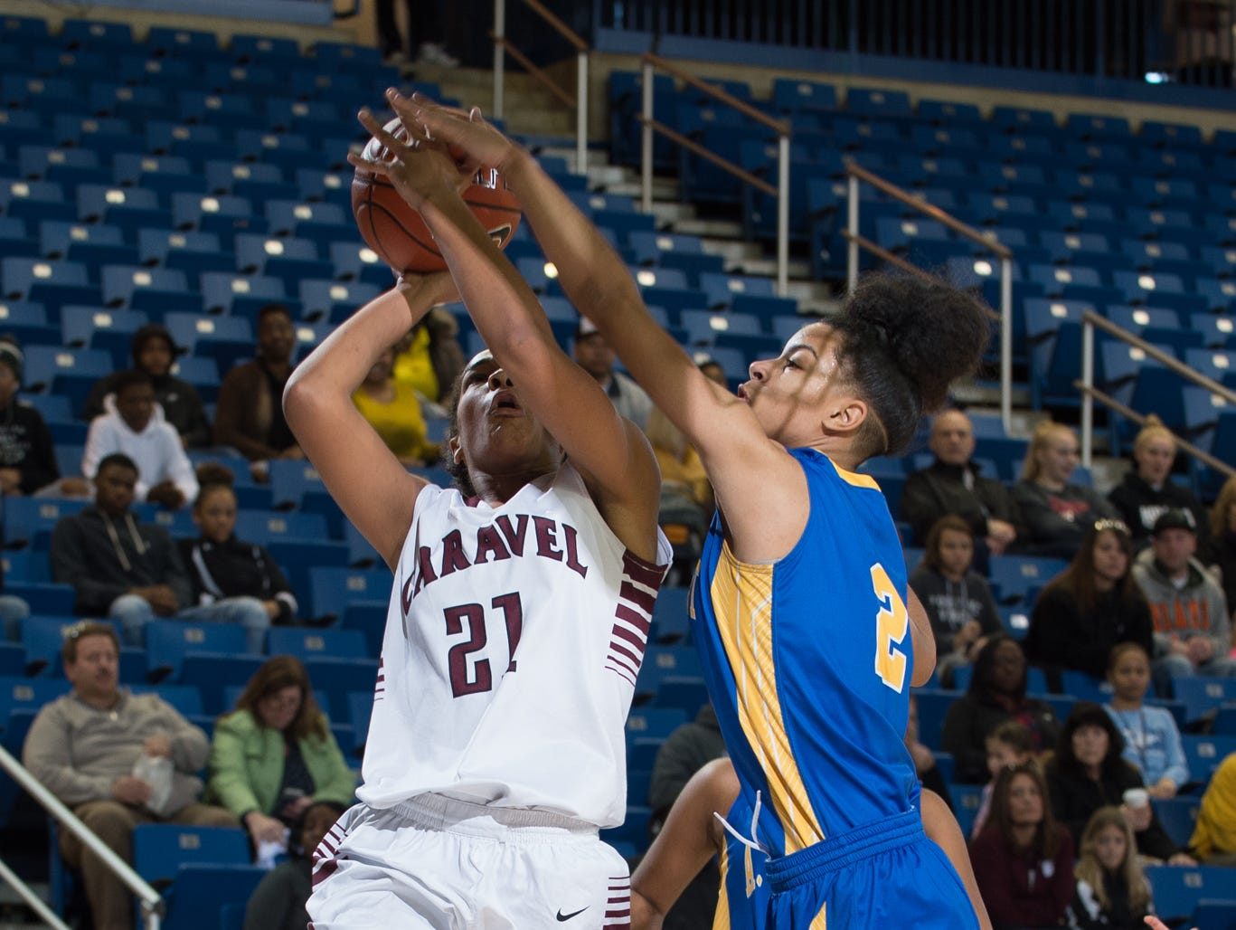 A.I. duPont's Lauryn Griffin (2) reaches to stop a shot by Caravel's Kaylee Otlowski (21) in the quarterfinals of DIAA Girls Basketball Tournament at the University of Delaware.