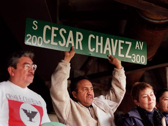 Alfonso Salas holds a Cesar Chavez Avenue sign at a rally in 2002. A portion of Grand River Avenue in Lansing's Old Town neighborhood was renamed  in honor of the labor leader in 2017.