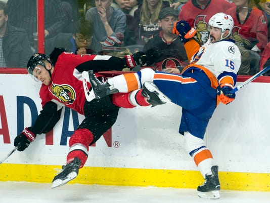 e9b86584e New York Islanders right wing Cal Clutterbuck (15) sends Ottawa Senators  defenseman Mark Borowiecki