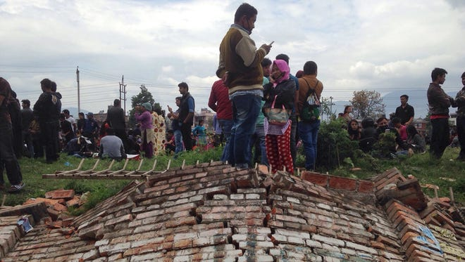 A group of people gather outdoors as an earthquake hits Kathmandu city, Nepal, Saturday, April 25, 2015. A strong magnitude-7.9 earthquake shook Nepal's capital and the densely populated Kathmandu Valley before noon Saturday, causing extensive damage with toppled walls and collapsed buildings, officials said. (AP Photo/ Niranjan Shrestha)