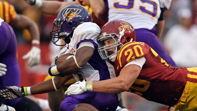 Iowa State's Jake Knott, right, makes a hit on Northern Iowa's Carlos Anderson during a 2011 ISU-UNI football game. Michael Gartner, a former president of the Iowa Board of Regents, says the University of Iowa and Iowa State could subsidize UNI athletics.
