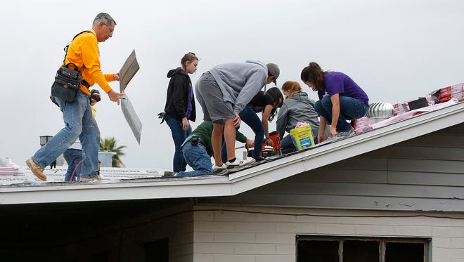 Habitat For Humanity house leader Joe Genovese (left)  helps reroof a home near near Grand Canyon University in February 2015.