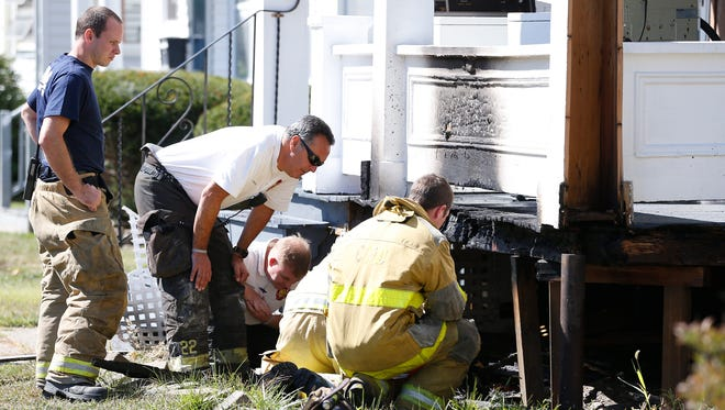 West Elmira Volunteer Fire Department officials survey the damage of a fire in the 900 block of West Gray Street Tuesday.