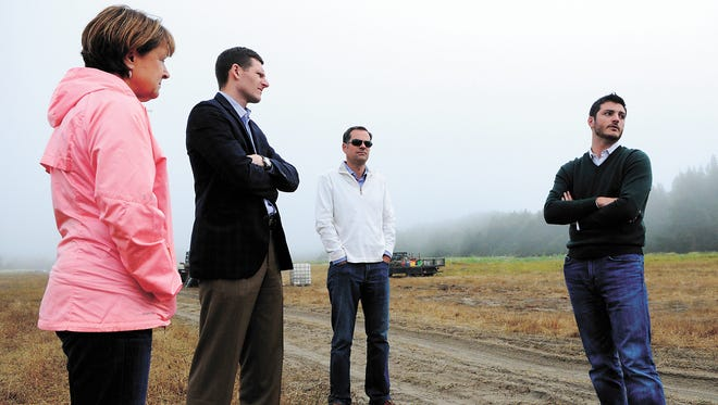 In this photo taken on Tuesday, Aug. 6, 2013, from right to left, Michael Hinrichs, Chuck Deister, Ray Bucheger and Rep. Caddy McKeown tour the Jordan Cove Energy Project site on the North Spit, in Coos Bay, Ore.