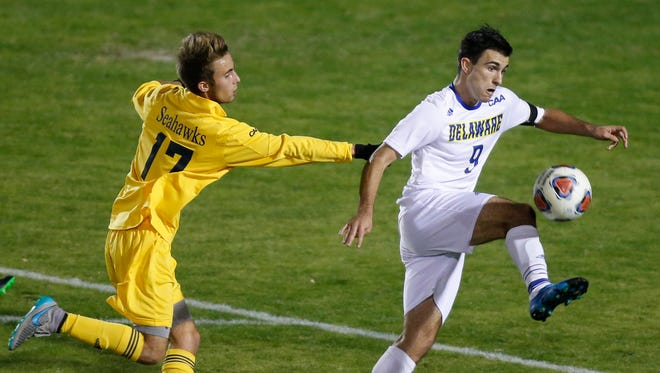 Delaware's Guillermo Delgado (right) turns to the net as he tries to control on the attack in front of UNC-Wilmington's Huntley Munn in the first half of a CAA championship quarterfinal at Grant Stadium Saturday.