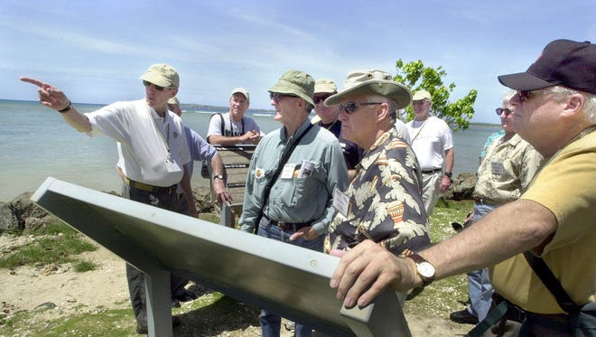 Participants in a tour by Military Historical Tours look around at Ga'an Point in Agat.