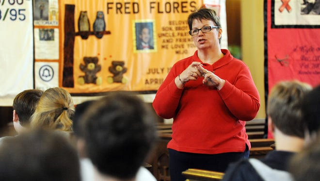 AIDS Services Coalition Executive Director Kathy Garner talks to students about the AIDS Memorial Quilt at Trinity Episcopal Church. The quilt honors those who have lost their lives to the AIDS pandemic. Since 1987, over 14 million people have visited the quilt at thousands of displays worldwide.