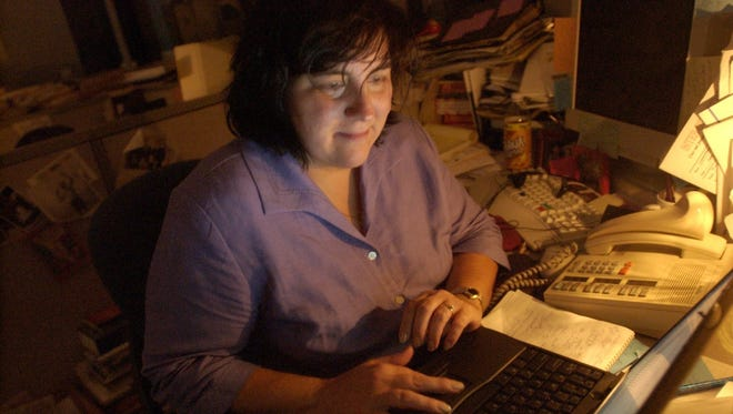 Patricia Montemurri writing at her desk during the Aug. 14, 2003 Blackout. Staffers worked by candlelight and flashlight..
