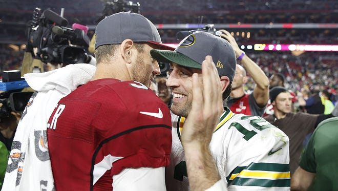 Green Bay Packers quarterback Aaron Rodgers shares a smile with Arizona Cardinals quarterback Carson Palmer after the Dec. 27 game at University of Phoenix Stadium.