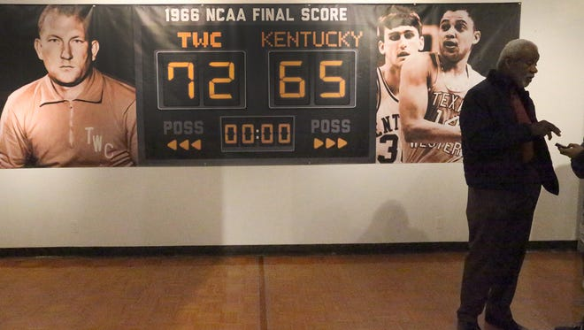 Nolan Richardson, right, a former UTEP basketbal player, Bowie HIgh School and Arkansas basketball coach, is silhouetted against an image of a scoreboard at an exhibit on the 1966 Texas Western College NCAA championship team Thursday on the UTEP campus.