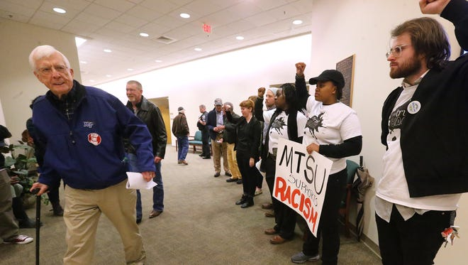 An unidentified man, left, in favor of keeping the name of MTSU's ROTC building as Forrest Hall, leaves a forum Wednesday night that was held about a name-change proposal. Supporters of a name change lined the hallway of Lane Agri-Park in Murfreesboro where the community forum was held.
