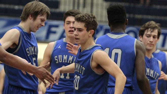 Teammates congratulate Sam Martin of Summit after he hits a buzzer beater three point play at the end of the first quarter.  Purcell Marian takes on Summit Country Day in the Division III Regional Semi-finals at Fairmont High School in Kettering, Ohio Wednesday March 9th, 2016.