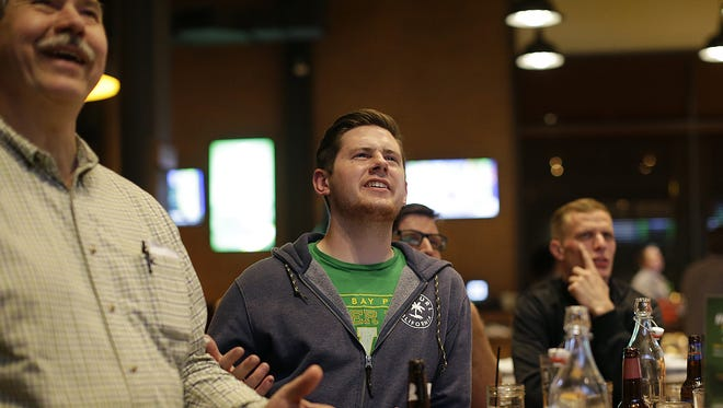 Zane Statz of Green Bay, middle, reacts after the Packers selected UCLA defensive tackle Kenny Clark in the first round while watching the NFL draft at 1919 Kitchen & Tap at Lambeau Field.