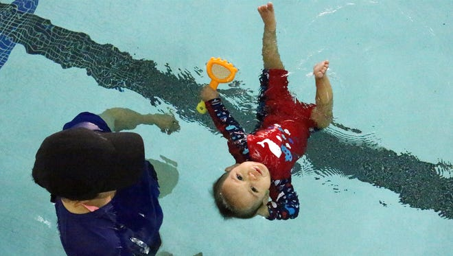 Matheo Rivera, 10 months, floats on his back as instructor Laura Castle watches at O'Rourke Aquatic Center. The toddler is learning what to do if he accidentally falls into water. Castle is a certified instructor of the Infant Swimming Resource's Self-Rescue program.