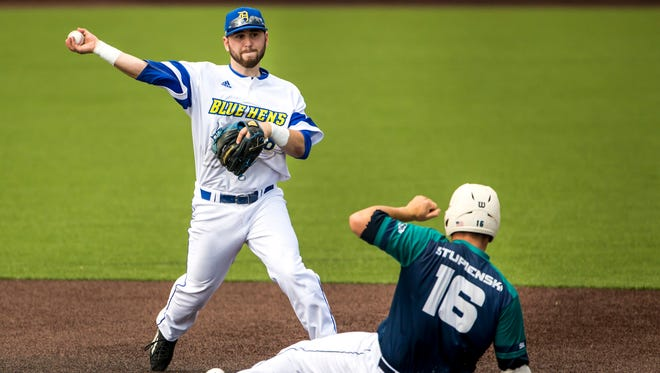 Delaware second baseman Jeremy Ake throws to first, after tagging out UNCW catcher Gavin Stupienski at second base, as he turns a double play in Delaware's 12-2 loss to UNCW at Hannah Stadium at the University of Delaware on Thursday afternoon.