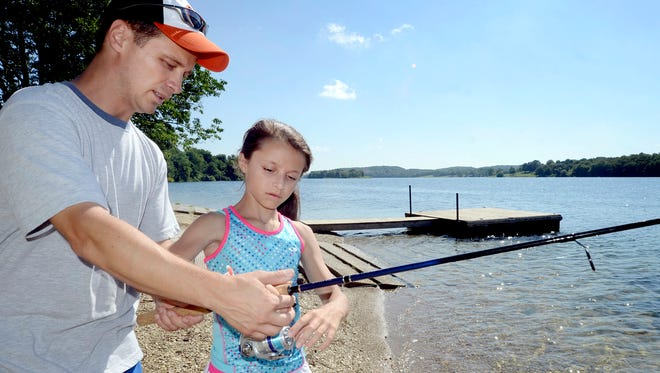 Bill Antoshak instructs his daughter Elizabeth, 13, on casting an open-face reel while fishing at Lake Marburg in Codorus State Park. Bill Kalina photo