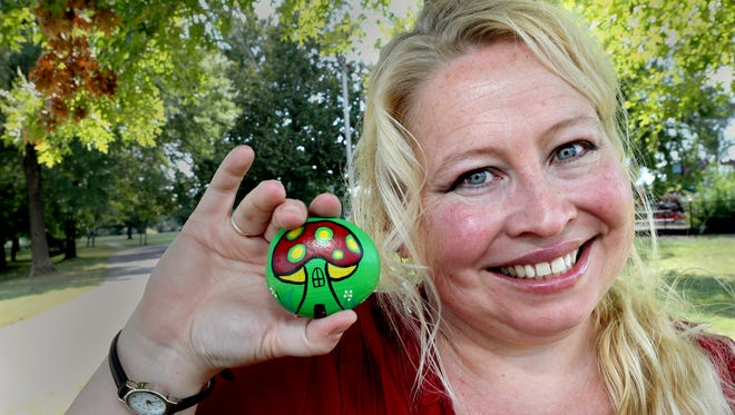 Monica Ashbaugh shows off one of her painted rocks at Old Fort Park on Thursday, Sept. 22, 2016, one of the places she places painted rocks in Murfreesboro.