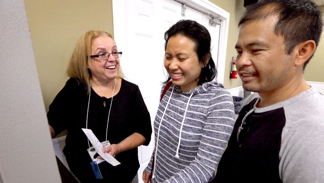 Poll worker Joyce Kittle, left, shows Pontip Sivongsa, center the voting procedure as she gets ready to vote for the first time ever, as her husband Aaron Sivongsa, right assists his wife by translating for her at the Middle Tennessee Association of Realtors, on the last day of early voting, Thursday, Nov. 3, 2016.