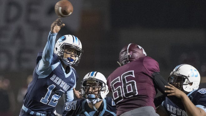 Redwood quarterback Frankie Ayon passes against Mt. Whitney in the annual Cowhide football game at Giant Chevrolet-Cadillac Mineral King Bowl on Friday, November 4, 2016.