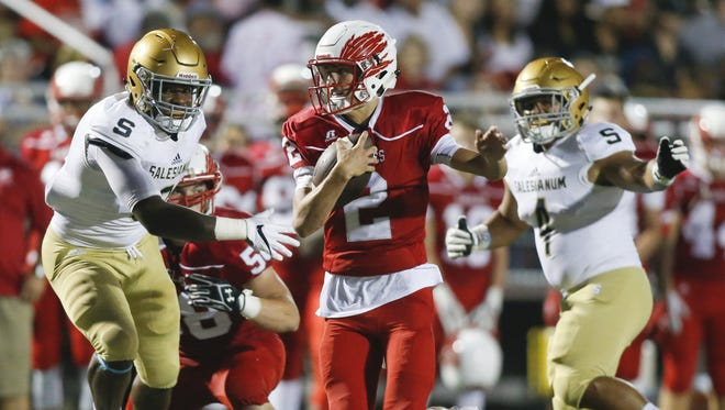 Smyrna quarterback Nolan Henderson scrambles past Salesianum defenders Josh Patrick (left) and William Vanneman on Sept. 23. Henderson has been named the state's Offensive Player of the Year.