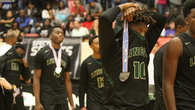 Lincoln's Tyler Farmer (10) reacts after accepting second-place medals after the Trojans lost the 8A state championship game to Tampa Sickles, 51-45, on Saturday night in Lakeland.