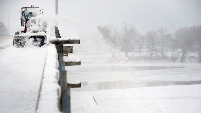 An Elmira city crew member clears the Walnut Street bridge on Wednesday.