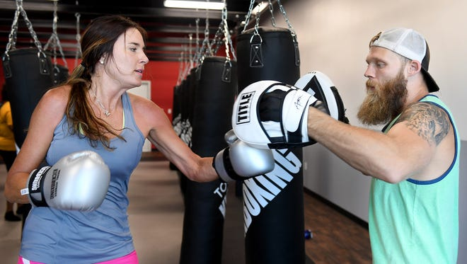 Meredith Figueroa works on her technique with former professional MMA fighter and director of opperations for Total Fitness Kickboxing Joe Pass.