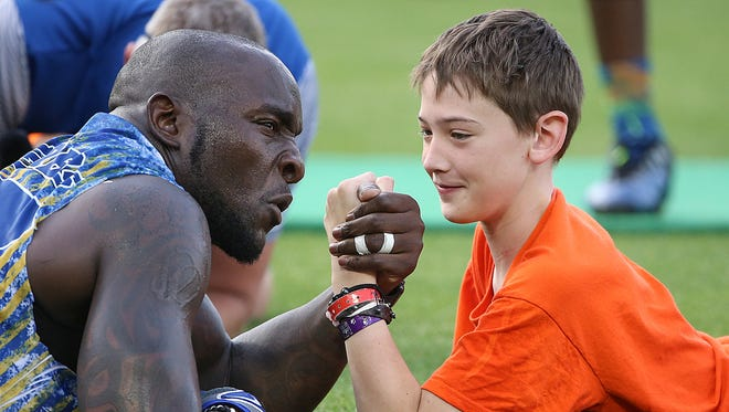 Indianapolis Colt Robert Mathis arm wrestles Mason Unton, 11, in the center of the diamond, during the 9th annual Caroline Symmes Celebrity Softball Challenge at Victory Field in Indianapolis, Thursday, June 15, 2017.