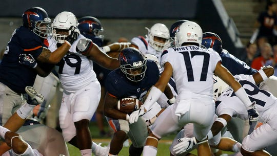UTEP tail back Walter Dawn Jr., looks for hole in the