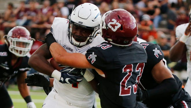 UTEP running back Quardraiz Wadley carries the ball as well as Aggie defensive back Ron LaForce for a couple of yards during first half action at Aggie Memorial Field in L:as Cruces, New Mexico. The Aggies went into the locker room with a 21-7 lead.