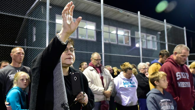 Jody Corbett, Shippensburg, lifts her hand in prayer during a  vigil service Monday, October 2, 2017.  William Wolfe, Shippensburg, is missing following the deadly shooting on Sunday during a concert in Las Vegas. Community members met at Doc Norcross Stadium in Shippensburg.