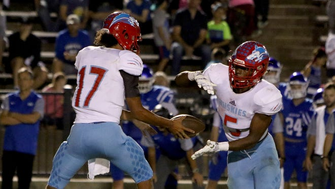 Hirschi quarterback Mar'tez Vrana hands the ball off to Daimarqua Foster in the game against Decatur Friday, Oct. 20, 2017, in Decatur at Eagles Stadium.