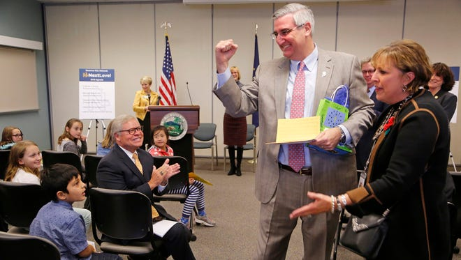 Gov. Eric Holcomb gives a fist pump to the students from Cumberland Elementary and Happy Hollow Elementary Wednesday, November 8, 2017, at Ivy Tech Community College. The students along with second grade teacher Maggie Samudio, right, have been pushing to have the Say's firefly named as the state insect. Holcomb, who was at Ivy Tech to announce his 2018 NextLevel Agenda, part of which is naming the Say's firefly the Indiana state insect.