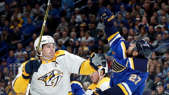St. Louis Blues' Alex Pietrangelo (27) reaches for a puck in the air along side Nashville Predators' Filip Forsberg, of Sweden, during the first period of an NHL hockey game Friday, Nov. 24, 2017, in St. Louis.