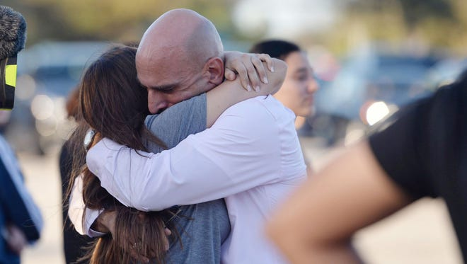 Families reunite after a mass shooting at nearby Marjory Stoneman Douglas High School in Parkland, Fla., on Wednesday, Feb. 14, 2018.