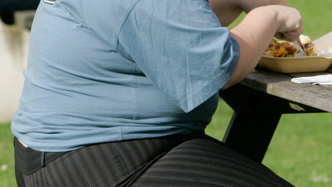 An overweight person eats at a bench.