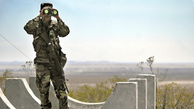 In this June 12, 2006, file photo, Army National Guard Spc. Gustavo Gutierrez, 23, of Las Cruces, scans the U.S./Mexico border from the top of Radar Hill, near Columbus, N.M.