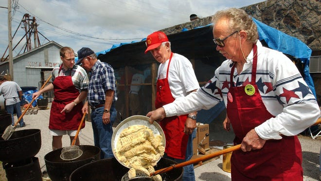 Ray Wilcox, right, fries up a batch of sucker fish at Sucker Day in Nixa. Wilcox has been cooking the fish for over 30 years. The photo is from 2003.