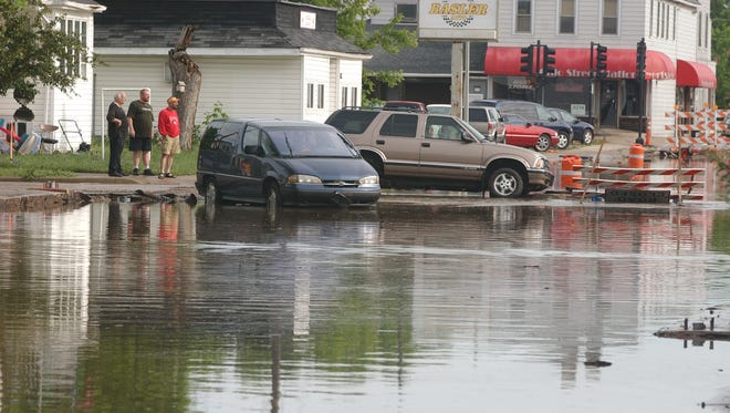 Friday people watch as the water still flows on Ohio Street near 10th Avenue.